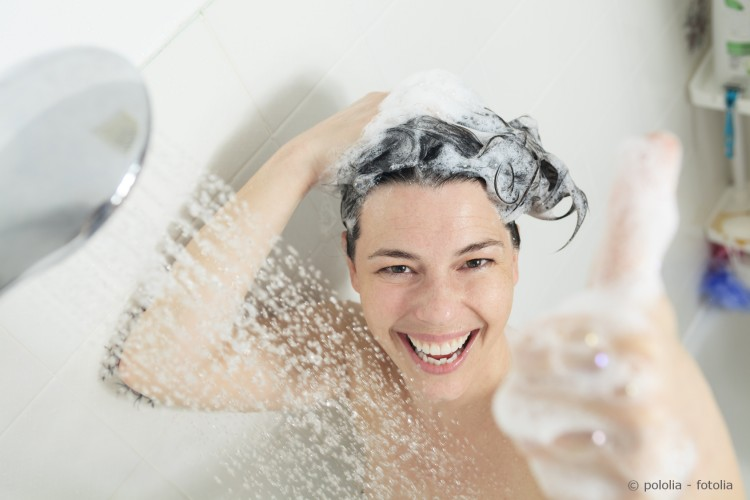 Frau duscht und lacht